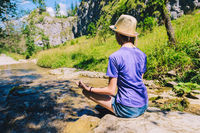 Young woman meditating in yoga pose at a mountain stream