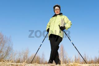 Frau stützt sich auf Nordic-Walking-Stöcke