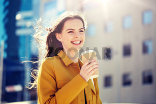happy young woman drinking coffee on city street