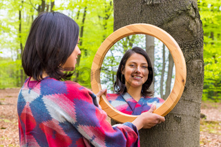 Woman looking at mirror in spring forest