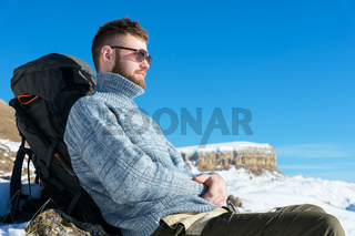 Portrait of a traveler hipster in sunglasses and a knitted gray sweater resting against the backdrop of a beautiful winter landscape with a table mountain in the snow