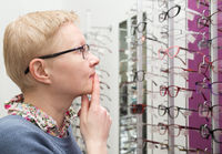 Mature woman chooses a new frame for glasses in the store optics
