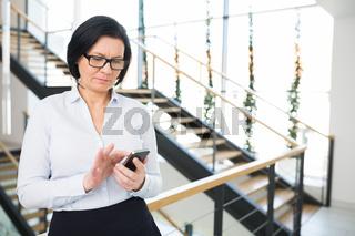 Business Frau tippt eine SMS auf ihrem Smartphone