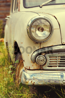 The old rusted machine. Front view where there is a spotlight with a grille and a bumper