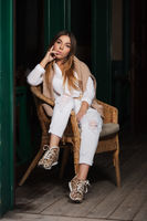Young fashion woman in white blouse sitting on wicker chair at sidewalk cafe