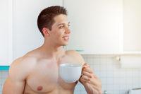 Bodybuilder junger Mann nachdenken Zukunft Textfreiraum Copyspace trinkt trinken Kaffee in der Küche