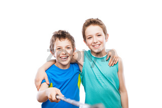Two smiling child boy brothers holding mobile phone or smartphone selfie stick taking portrait photo