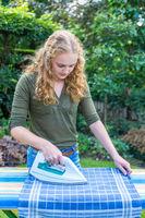 Young dutch woman ironing tea towel outdoors