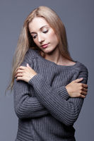 Portrait of young woman in gray woolen sweater with hands crossed. Beautiful girl posing on grey studio background. Female with blonde hair and day beauty makeup