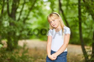 Blondes Mädchen steht schüchtern im Grünen