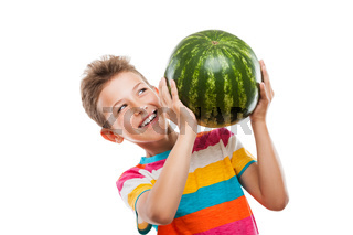 Handsome smiling child boy holding green watermelon fruit