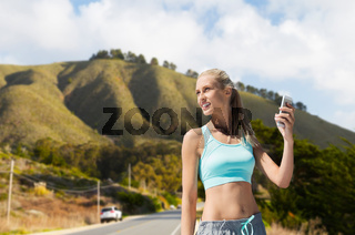 woman with smartphone doing sports over hills
