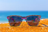 Colorful sunglasses with blue sea