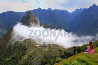 Woman enjoying the view of Machu Picchu citadel in Peru