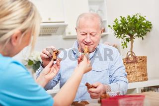 Altenpflegerin hilft Senior mit Demenz