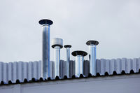 Five chimney pipe from stainless steel on the roof of the house.