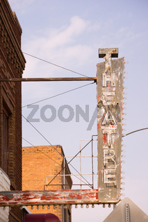 Old Vertical composition metal neon theater sign against blue sky