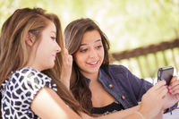 Expressive Young Adult Girlfriends Using Their Smart Cell Phone Outdoors