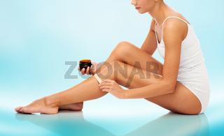 beautiful woman applying depilatory wax to her leg
