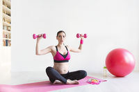 One young pregnant woman doing fitness exercises