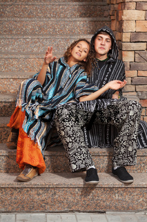 Young fashion hippie couple sitting on the steps