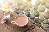 hot tea in white cup with flowers on wooden pebble stone water background