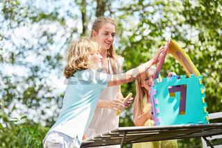 Mutter und Kinder bauen ein Puzzle Haus