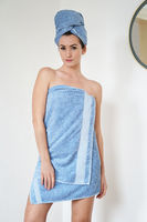 young woman wrapped in blue towel at home