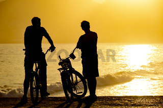 Two cyclists during late afternoon