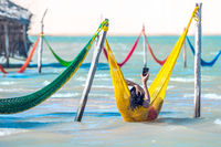 Woman relaxing on hammock and do selfie on vacation, Jericoacoara, Brazil