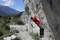 Sportler klettert an Naturfels