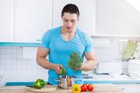Junger Mann kochen Essen zubereiten Gemüse Mittagessen in der Küche gesunde Ernährung