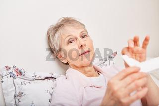 Frau nimmt Tabletten aus Tablettenspender