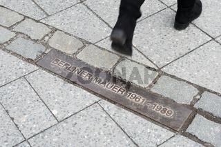 pedestrian walking across commemorative plaque for Berlin Wall