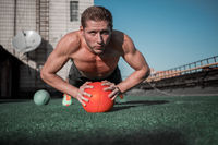 Front view of man standing in plank with hands on the ball.