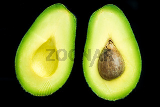 Avocado halves on dark background,flat lay