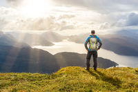 Man reaching summit enjoying freedom. Stunning view to coastal mountains and fjords. Hellandsnuten, Sandsfjord, Norway.