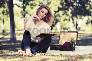 Young fashion woman reading a book in city park