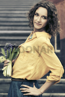 Happy young fashion woman with bouquet of flowers