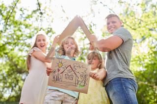 Kinder mit Zeichnung vom Eigenheim als Vision