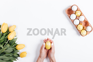 Top view of female hands holding yellow Easter egg near tulips