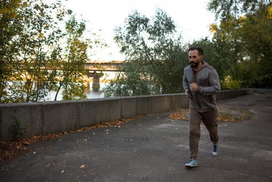 View of man running on river bank in the city.