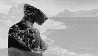 Silhouette of a naked woman combined with a rocky coast and sea. Double exposure. Black and white