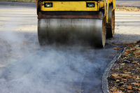 Mini compactor tires the upper layer of asphalt in the construction of a bicycle lane. Steaming hot asphalt, reportage shooting.
