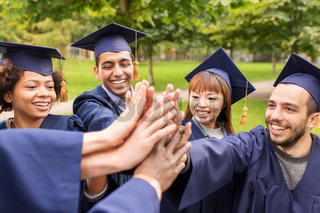 happy students in mortar boards making high five