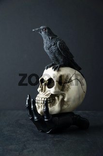 Skull with black bird in skeleton hand