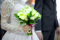 Bouquet of roses in the hands of the bride with shallow depth of field