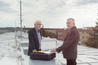 Senior businessmen making a business deal on the roof of a building
