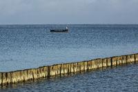 Buhnen in einer Bucht von Boltenhagen mit einem Boot im Hintergrund