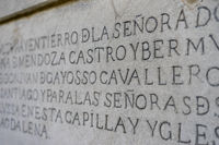 ancient writing in latin and ancient spanish carved on the stone inside a gothic cathedral in spain